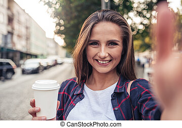 Young woman taking a selfie in the city