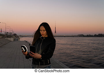 Young woman taking a selfie using a ring flash as a fill light at a sunset with a view over river Daugava