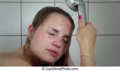 Young woman taking a shower. Close up on here face while...