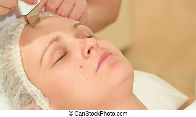 Young woman taking facial treatments of ultrasonic cleaning...