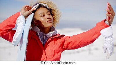 Young woman taking her selfie with a snowboard - Young woman...