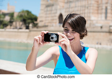 Young woman taking holiday photos