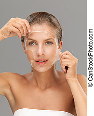 young woman taking off peeling mask - young woman peeling...