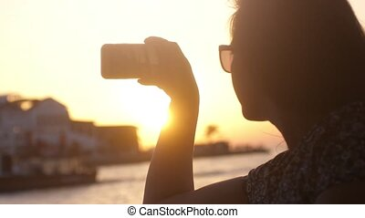 Young woman taking photo against impressive sunset during...