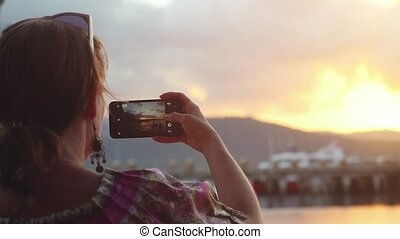 Young woman taking photo of the sunset with her phone in slow motion on tropical beach of Koh Samui.