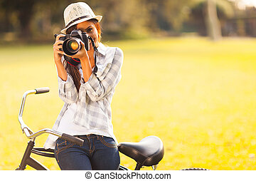 young woman taking photo outdoors - smiling young woman...