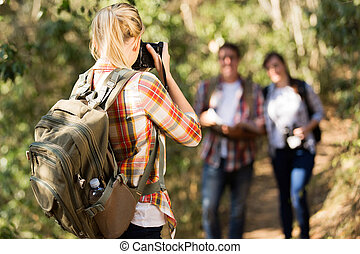 young woman taking photos of her friends in mountain