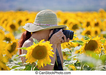 Young woman taking photos of sunflowers. - Attractive female...