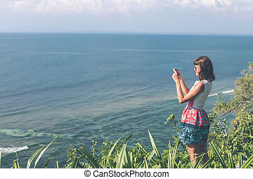 Young woman taking photos on the cliff with a beautiful ocean background at sunny day. Bali island.