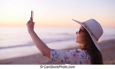 Young woman taking photos with her smartphone on beach