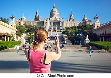 Young woman taking picture of Catalan National Art Museum (MNAC), housed in the Palau Nacional dating to 1929 will mobile phone. Barcelona, Spain.