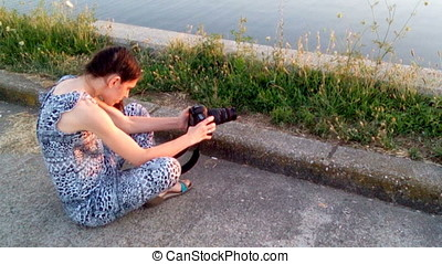 Young Woman Taking Pictures Of Lake At Sunset