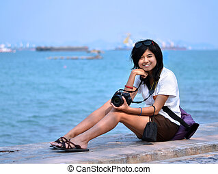 Young woman taking pictures on the beach