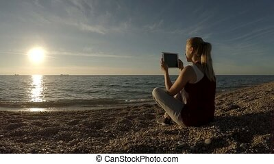 Young Woman Taking Pictures On The Beach Using Tablet