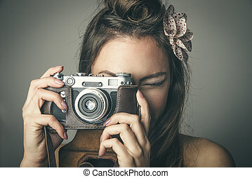 Young woman taking pictures with vintage camera