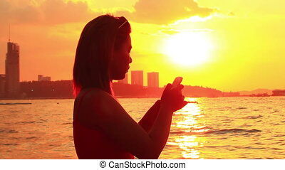 young woman taking selfie at beach at sunset