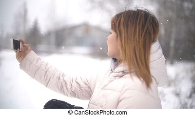 Young Woman taking selfie during snowfall. Slowmotion