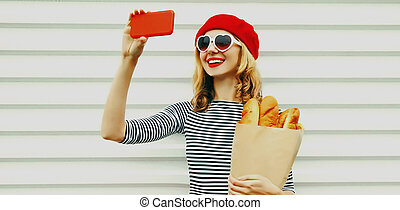 young woman taking selfie picture by phone holding grocery shopping paper bag with long white bread wearing a french red beret over a white background