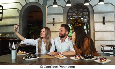 Young woman taking selfie with friends in restaurant