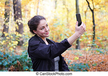 young woman taking selfie with smartphone in forest