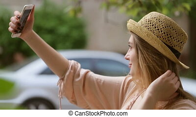 Young woman taking selfies on the street.