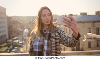 Young woman taking selfies via her smartphone on the balcony of her apartment.