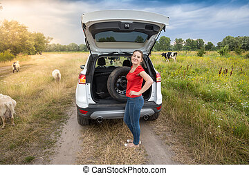 Young woman taking spare wheel out of car trunk on countryside road