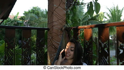 Young Woman Talk On Phone Call Lying In Hammock Using Cell...