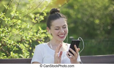 Young woman talking by smartphone in park