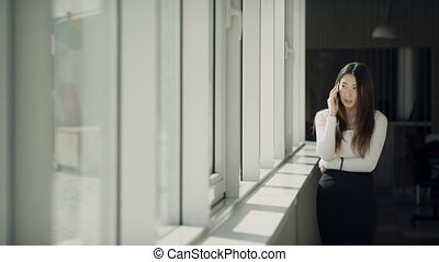 Young woman talking on cell, standing near window inside office.