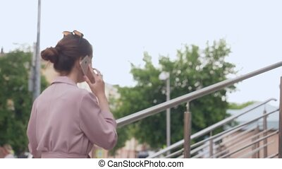 Young woman talking on her cell phone on the street.