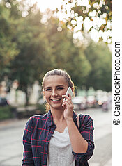 Young woman talking on her cellphone in the city
