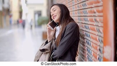 Young woman talking on her mobile in town