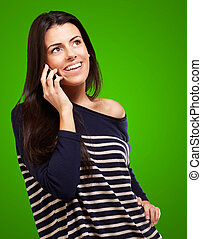 Young woman talking on mobile over green background
