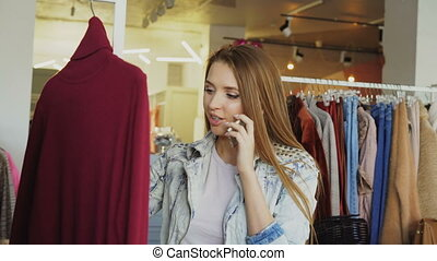 Young woman talking on mobile phone and choosing clothes in...