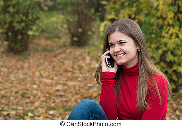 Young woman talking on mobile phone in fall