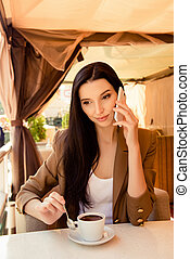 Young woman talking on phone at dinner with cup of coffee
