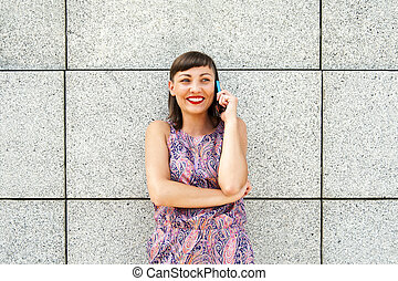 Young woman talking on phone by the wall in city smiling.