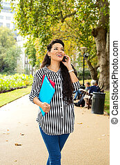 young woman talking on the phone holding folders.