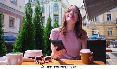 young woman talking on the phone in a cafe on a summer ...