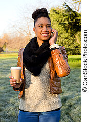 young woman talking on the phone in a park.