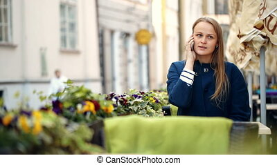 Young woman talking on the phone in outdoor cafe
