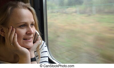 Young woman talking on the phone while traveling by train