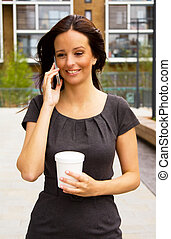 young woman talking on the phone with a coffee cup