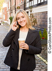 young woman talking on the phone with a coffee