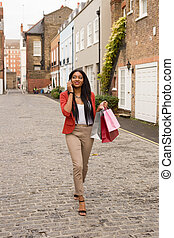 young woman talking on the phone with shopping bags