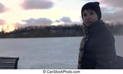 Young woman talking to camera in the winter park