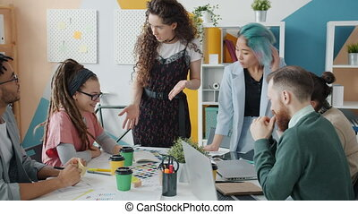 Young woman talking to group of creative designers sharing ideas on project in office