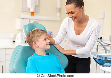 young woman talking to her son in dentist office