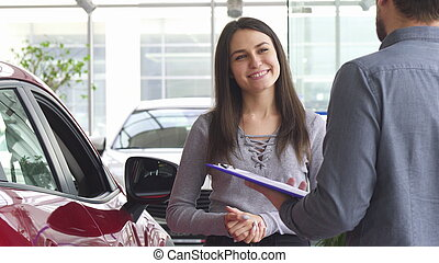 Young woman talking to the salesman at the car dealership